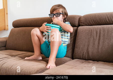 Boy sitting on couch at home wearing 3d glasses and eating popcorn - Stock Photo