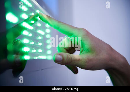 Detail of finger touching green led touchscreen - Stock Photo