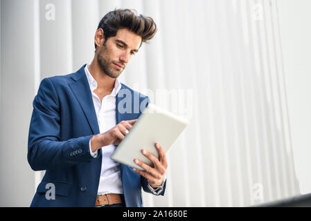 Businessman using tablet outdoors in the city - Stock Photo