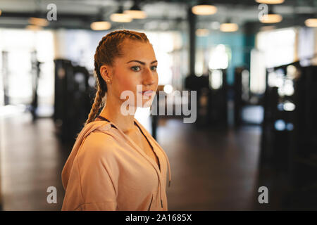 Portrait of young woman in a gym - Stock Photo