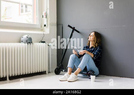 Young woman with e-scooter sitting on floor, using digital tablet - Stock Photo