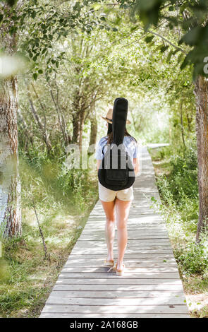 Rear view of young woman with guitar case walking on wooden walkway