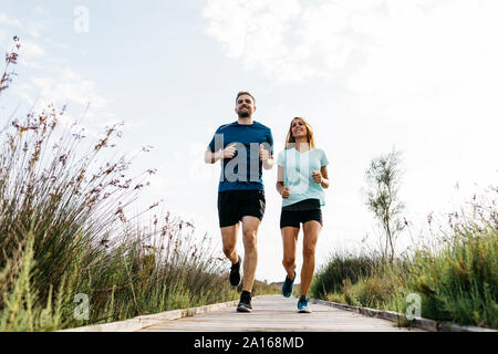Young couple jogging on wooden walkway - Stock Photo