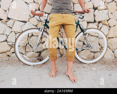 Barefoot man with Fixie bike in front of natural stone wall on the beach, partial view