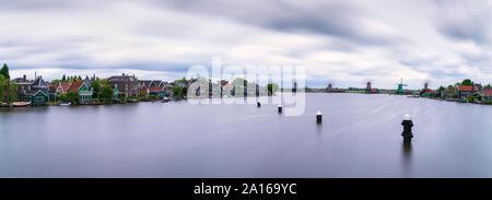 Panoramic shot of Zaan river against cloudy sky, Zaanse Schans, Zaandam, Netherlands - Stock Photo