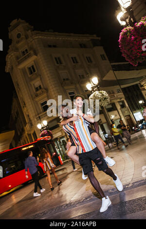 Young man carrying girlfriend piggyback at night in the city - Stock Photo