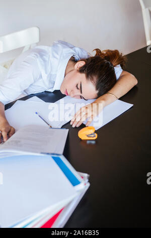 Exhausted female student lying on desk at home with documents - Stock Photo