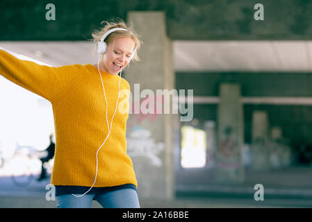 Portrait of singing and dancing young woman listening music with headphones