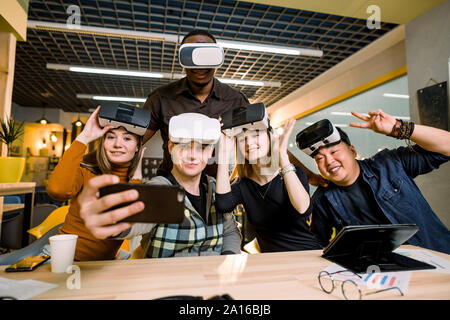 Young group of multiethnical people having fun with vr headset. Caucasian girls and man, African and Chinese men sitting at the desk and trying vr - Stock Photo