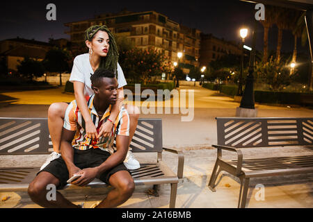 Cool young couple on a bench at night in the city - Stock Photo