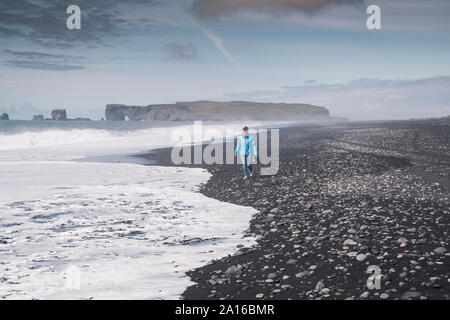 Young woman walking on barefoot on a lava beach in Iceland Stock Photo