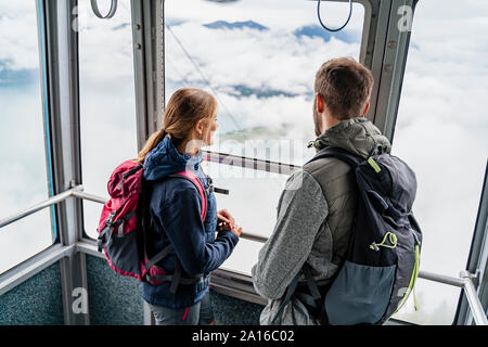 Young couple in a gondola cableway looking out of window, Herzogstand, Bavaria, Germany - Stock Photo