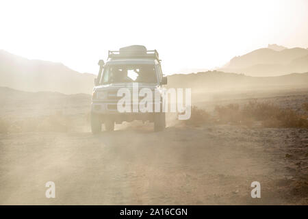 Off-road vehicle on dirt road amidst dust in desert against sky during sunset - Stock Photo