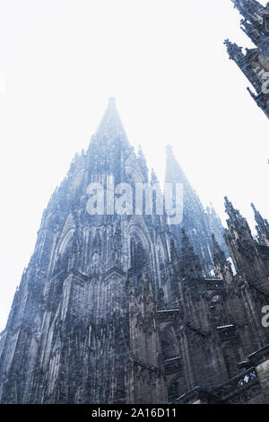 Low angle view of historic Cologne Cathedral in city during snowfall against sky