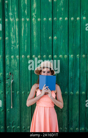 Portrait of young woman standing in front of green wooden door with a book in summer - Stock Photo