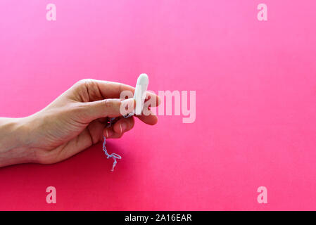 Hygienic tampon for women in hand on pink background. Menstruation or periods concept - Stock Photo