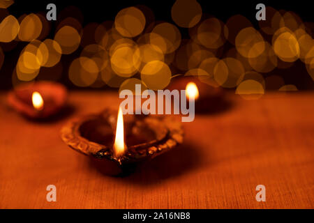 Clay diya oil lamps lit during diwali celebbration with bokeh lights in dark black background. Greetings card design for Indian Hindu light festival c - Stock Photo