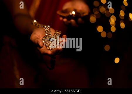Woman hand holding gold necklace jewelry on Diwali Festival or Dhanteras. Concept for newly weds bride jewellery, festive gift, diwali bumper offer, h - Stock Photo