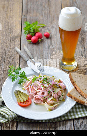 Hearty Bavarian sausage salad with cheese strips, pickles and rustic farmhouse bread served with a cool wheat beer - Stock Photo