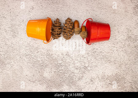 Red and orange buckets and pine cones on the table - Stock Photo