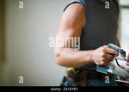 Male builder carrying a construction tool. - Stock Photo