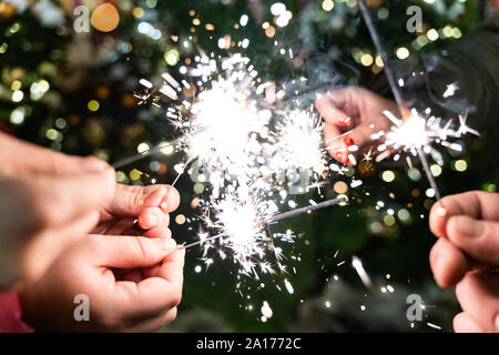 Group of friends burning Bengal lights during winter time celebrations, Christmas, New Year's Eve. - Stock Photo