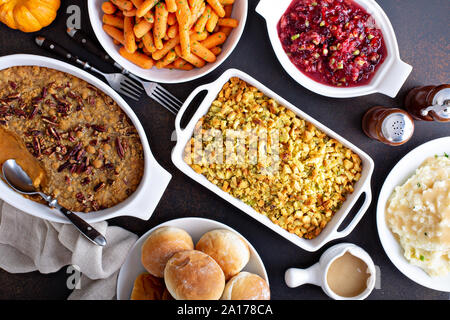 Variety of Thanksgiving sides on the dinner table, carrots, mashed potatoes, sweet potato casserole and stuffing - Stock Photo