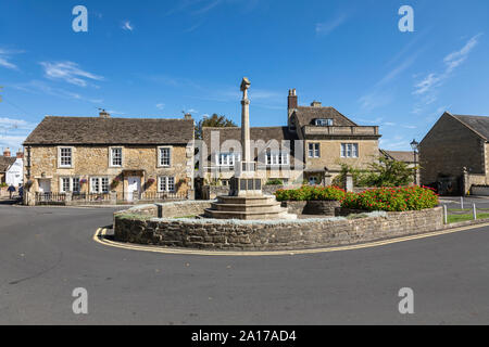 Melksham War Memorial with traditional stone built cottages in the background, Canon Square, Melksham, Wiltshire UK - Stock Photo