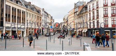 LILLE, FRANCE - APRIL 15, 2017: Shopping and sightseeing people along the Rue Esquermoise and Place du General de Gaulle with shops. The street and th - Stock Photo