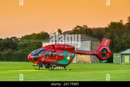 PONTYPRIDD, WALES - SEPTEMBER 2019: Wide angle view of  an emergency helicopter of the Wales Air Ambulance service on the ground near houses - Stock Photo
