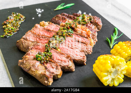Sliced medium rib eye beef steak meat with chimichurri on black background - Stock Photo