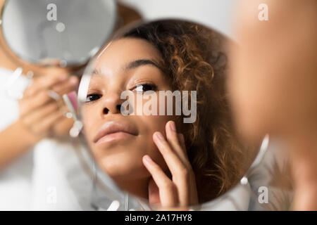 Afro Woman Looking In Mirror Touching Face At Bathroom