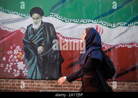 Tehran, Iran. 24th Sep, 2019. People walk past a mural painting showing the founder of the Islamic republic Ayatollah RUHOLLAH KHOMEINI and the national flag along the wall of the former US embassy in Tehran, Iran. Credit: Rouzbeh Fouladi/ZUMA Wire/Alamy Live News - Stock Photo