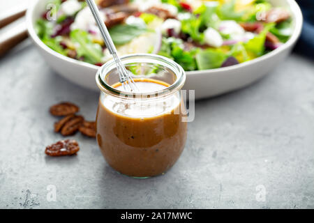 Balsamic vinaigrette dressing for a salad, small glass jar with a whisk - Stock Photo