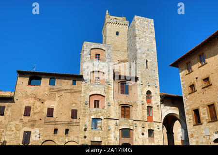 The Torre Grossa and buildings in the Piazza Cisterno in San Gimignano, Tuscany, Italy - Stock Photo