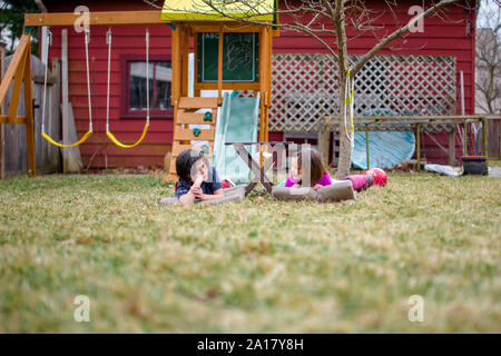 Two happy children lay on mats in their yard chatting together - Stock Photo