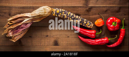 Dried multicolored corn cob with an assortment of fresh peppers on a dark wood background - Stock Photo