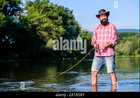 fly fish hobby. Summer fishery activity. fisherman in lake water. hipster fishing with spoon-bait. big game fishing. relax on nature. mature bearded man with fish on rod. He is ready for the fishing. - Stock Photo