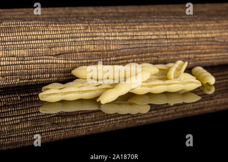 Lot of whole uncooked pasta cavatelli with brown textil cloth isolated on black glass - Stock Photo