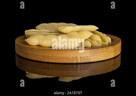 Lot of whole uncooked pasta cavatelli on bamboo plate isolated on black glass - Stock Photo