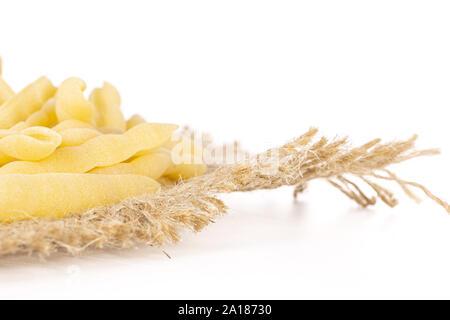 Lot of whole uncooked pasta cavatelli closeup on jute cloth isolated on white background - Stock Photo