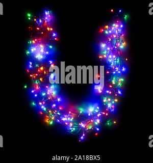 The letter 'U' of the English alphabet from a multi-colored electric garland on a black isolated background. New Year's alphabet.Wreath of colored bul - Stock Photo