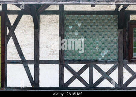 Frontal part view on an old half-timbered house with window from leaded windows. - Stock Photo