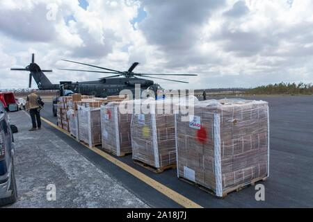 190911-F-XP529-0072    NASSAU, Bahamas – U.S. Navy Sailors and U.S. Air Force Airmen load four thousand pounds of Meals Ready To Eat (MRE's) onto a MH-53E Sea Dragon in Marsh Harbour, Bahamas, Sept. 11, 2019. U.S. Northern Command provided military-unique capabilities to the U.S. Agency for International Development, enabling the broader relief efforts addressing the acute humanitarian needs of the Bahamian people.  (U.S. Air Force photo by TSgt. Paul E. Cook) - Stock Photo