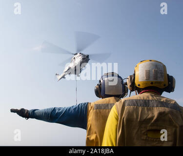 190912-N-IQ884-1239  RED SEA (Sept. 12, 2019) Aviation Boatswain's Mate (Handling) 1st Class Joseph Martinez, assigned to amphibious assault ship USS Boxer (LHD 4), signals a Military Sealift Command SA-330J Puma helicopter with Aviation Boatswain's Mate (Handling) Airman Johnny Snowden, also assigned to Boxer, on the flight deck during a vertical replenishment-at-sea. Boxer is part of the Boxer Amphibious Ready Group and 11th Marine Expeditionary Unit and is deployed to the U.S. 5th Fleet area of operations in support of naval operations to ensure maritime stability and security in the Centra