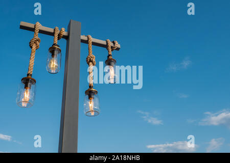 Decorated Lanterns on blue sky background. Tourism in Europe. Greece, island. Beautiful view of blue sky from greek tavern. Decorative lights hanging outdoor near cafe. Traveling background - Stock Photo