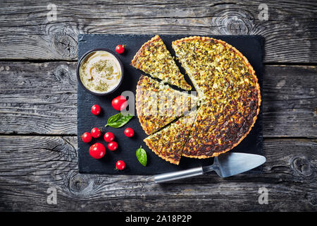 sliced quiche with green onions and spinach on a black slate tray with savory dip and tomatoes, view from above, flatlay - Stock Photo
