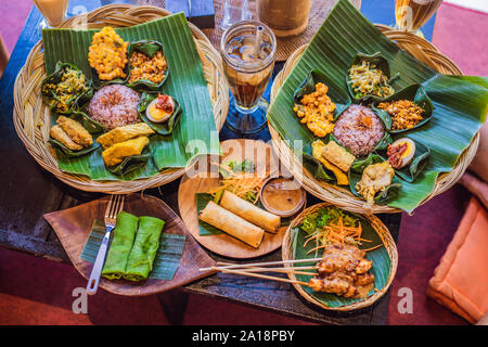 Nasi lemak, Nasi campur, Indonesian Balinese rice with potato fritter, sate lilit, fried tofu, spicy boiled eggs, and peanut - Stock Photo