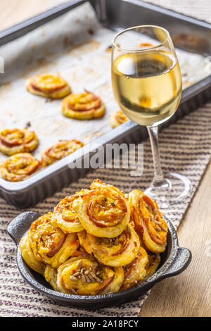 Rolls of puff pastry with ham bacon cheese sesame in dish