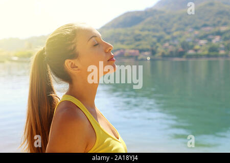 Portrait of a young woman breathe deeply outdoors on lake in a sportswear, head up, her eyes closed. Copy space. - Stock Photo